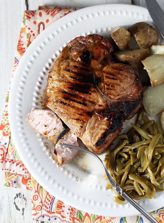 Overhead view of a grilled pork chop on a plate with green beans and potatoes.
