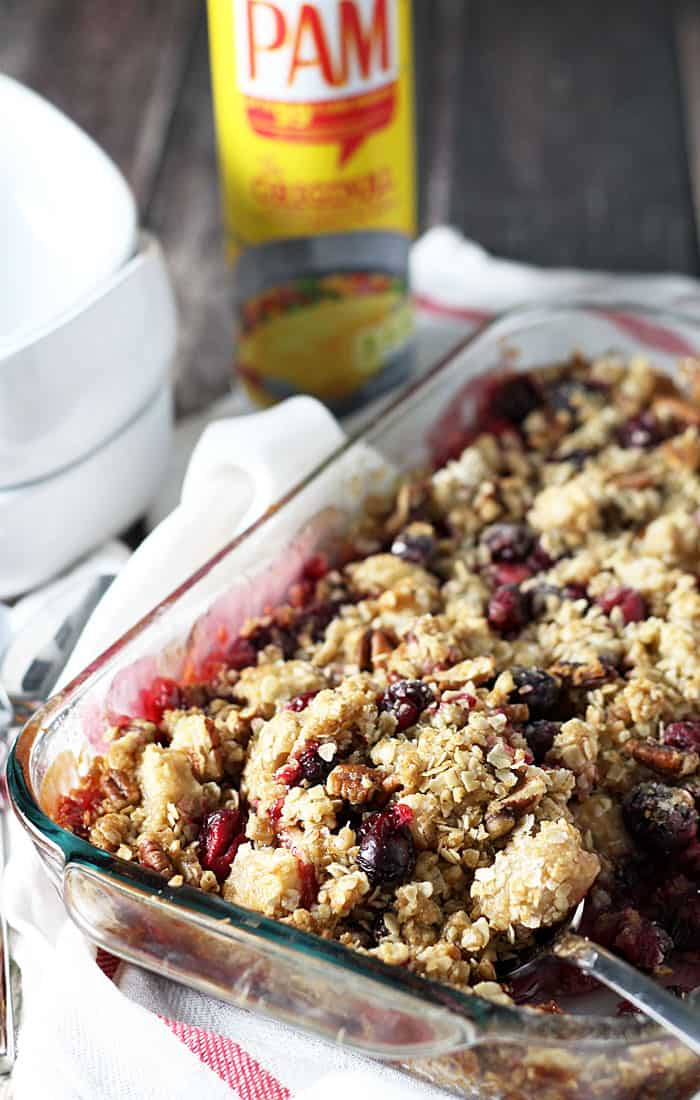 Cranberry Apple Crisp in a baking dish with a serving spoon by a striped napkin.