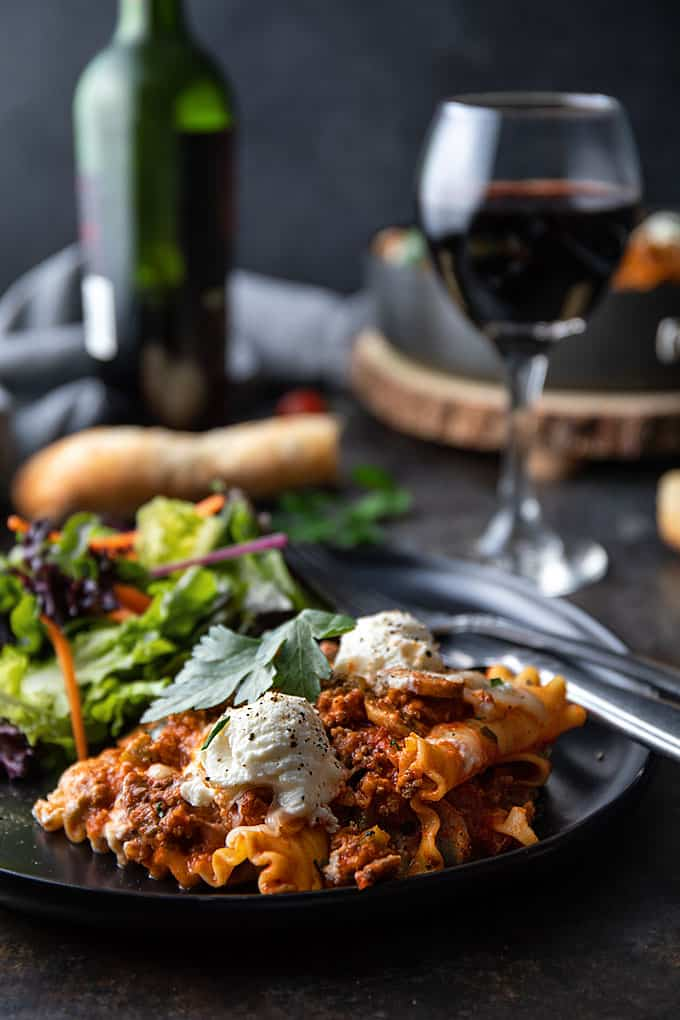 One skillet lasagna and salad on a round black plate with a fork.
