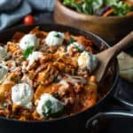 Lasagna in a large skillet with a wooden spoon and salad in a wooden bowl.