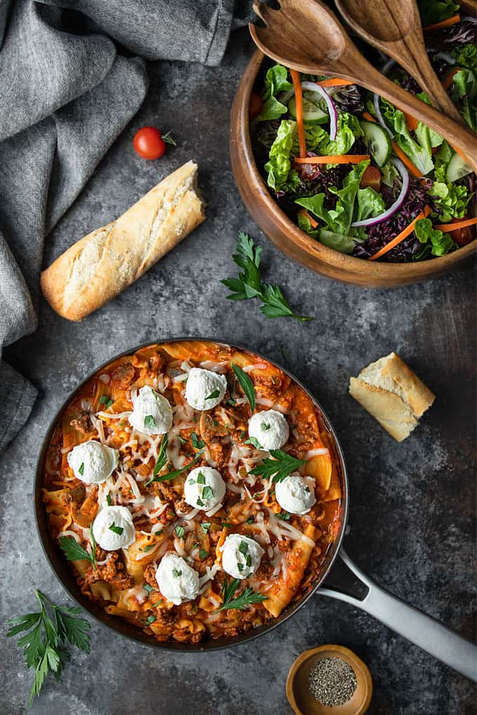 Lasagna topped with dollops of ricotta cheese in a skillet, French bread and a salad in a wooden bowl.