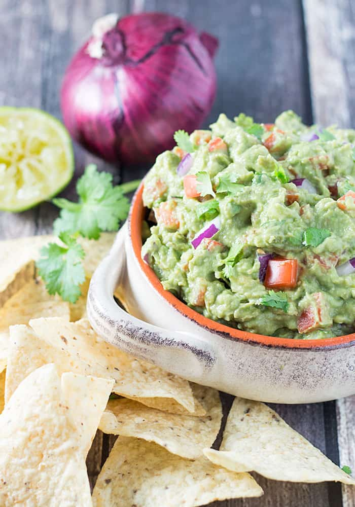 Guacamole in a tan bowl beside tortilla chips. An onion and a lime are in the background.