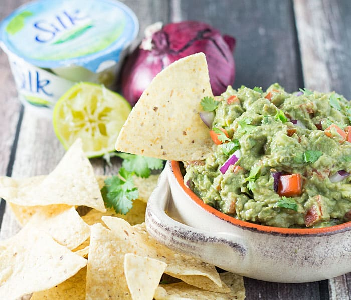 A bowl of guacamole with a tortilla chip in the bowl. A container of yogurt, onion and lime are in the background.