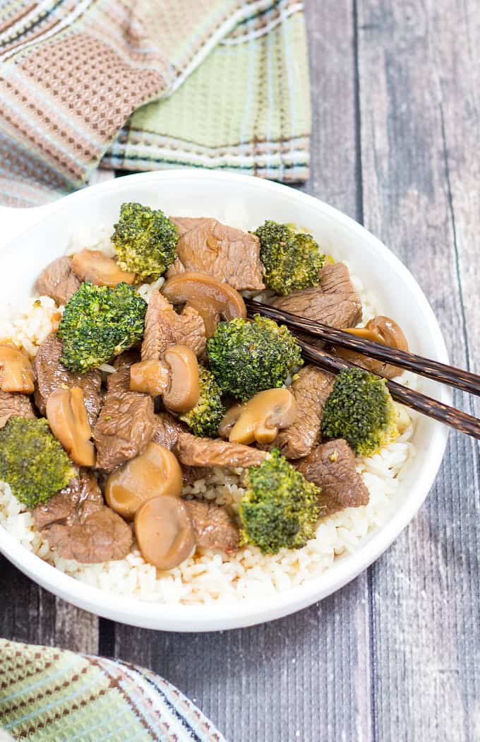 Overhead view of beef and broccoli over rice in a white bowl with chopsticks.