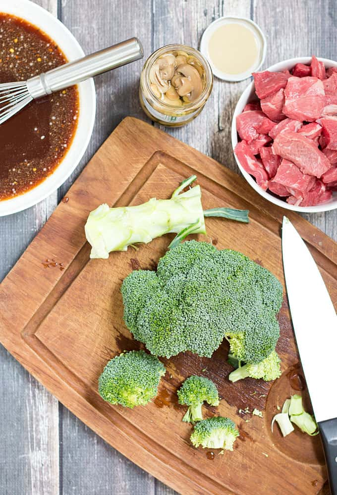 Overhead view of fresh broccoli, beef, a bowl of sauce mixture and a jar of mushrooms.