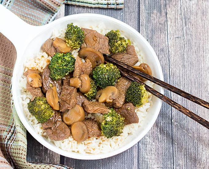 Beef, broccoli and mushrooms over rice in a white dish with chopsticks.