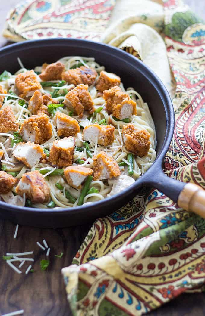 Breaded chicken pieces with asparagus, bacon and mushrooms over creamy pasta in a skillet.