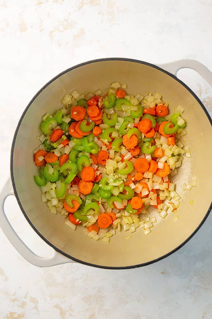 Overhead view of a white dutch oven with sauteed carrots, celery, onion and garlic.