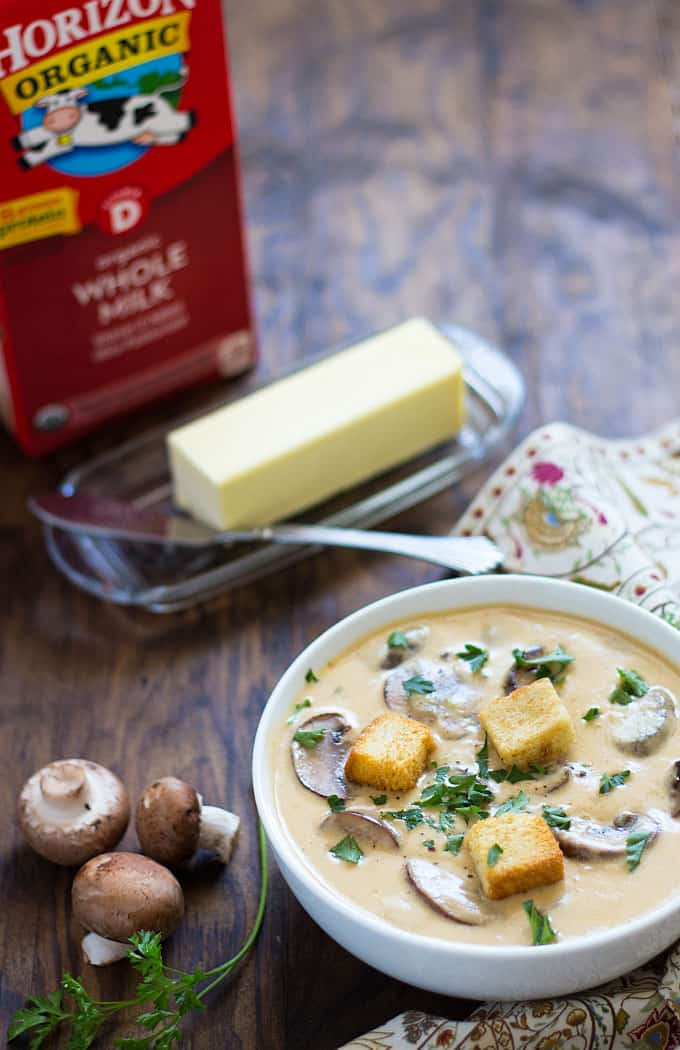 Mushroom soup in a white bowl. A tray of butter and a carton of milk are in the background.