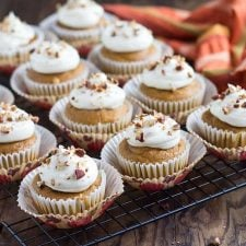 Cupcakes topped with cream cheese frosting and chopped pecans on a baking rack.