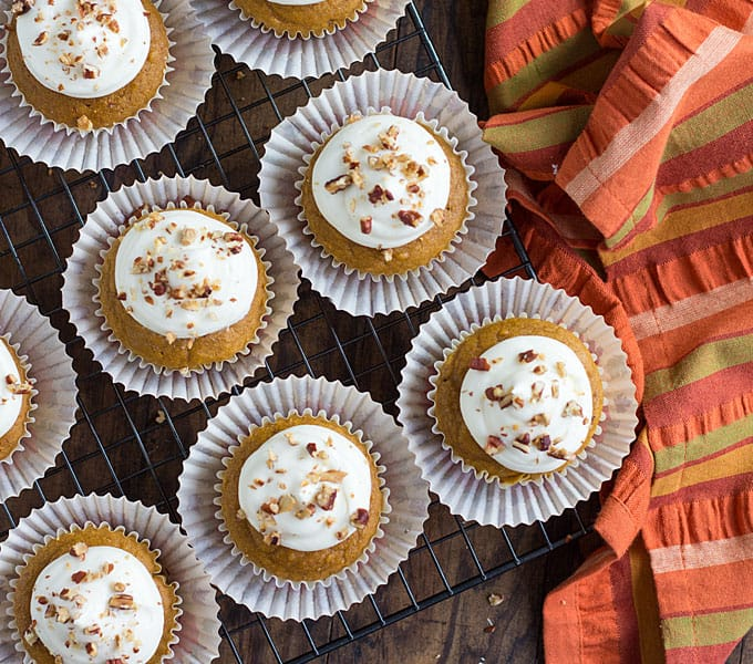 Overhead view of frosted pumpkin spice cupcakes on a baking rack by a striped napkin.