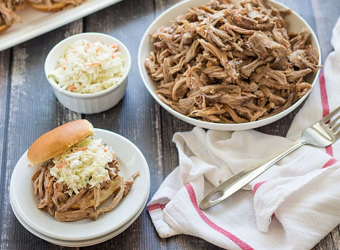 A barbecue sandwich with coleslaw on a plate beside a bowl of shredded pork and coleslaw.
