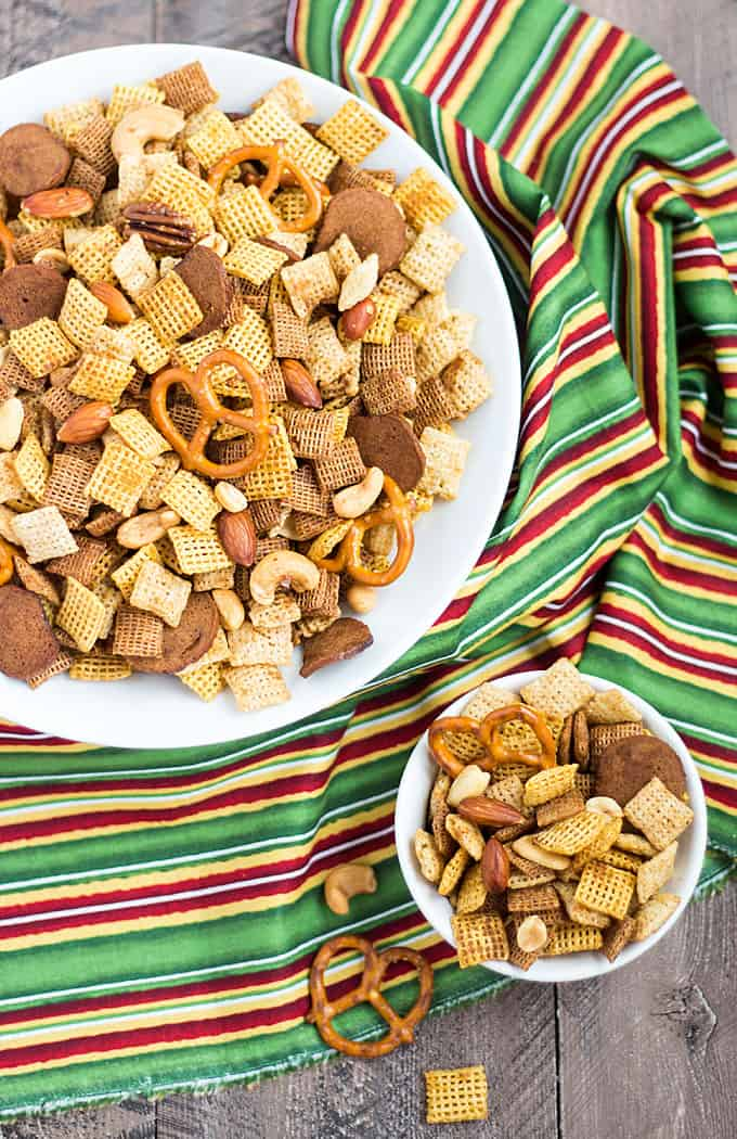 Overhead view of chex snack mix in a large and small white bowl over a striped napkin.