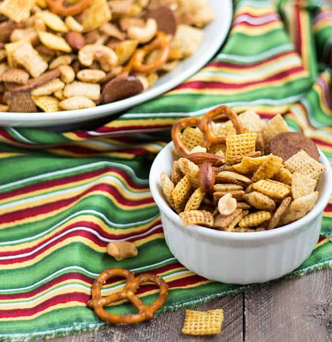 Closeup view of party mix in a small white bowl on a striped napkin.