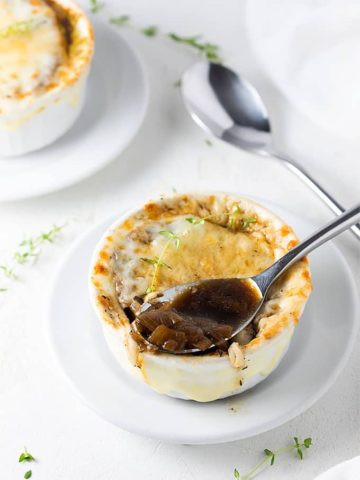 A spoon in a white bowl of onion soup on a white plate.