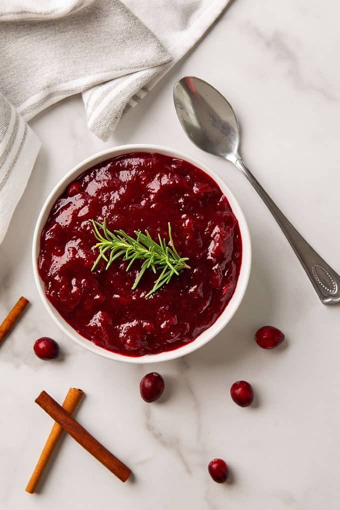 Fresh cranberry sauce in a white bowl beside a serving spoon