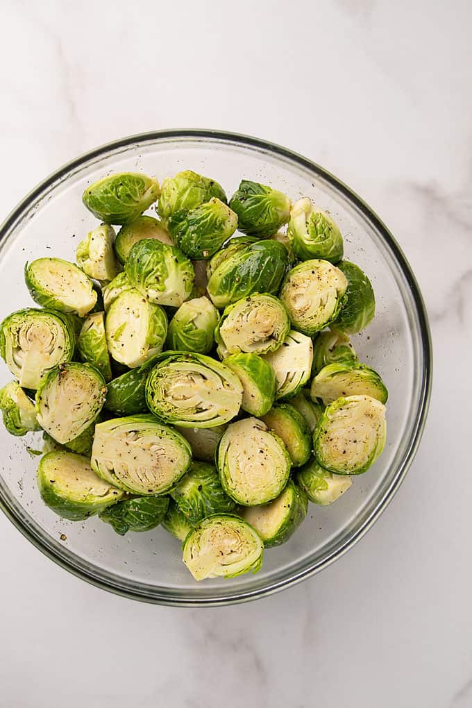 Raw Brussels sprouts tossed with oil and seasonings in a clear glass bowl