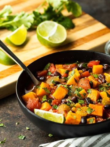 Sweet Potato and Black Bean Chili topped with chopped cilantro in a black bowl.