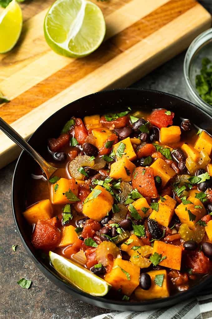 Sweet Potato and Black Bean Chili in a black bowl topped with chopped cilantro.