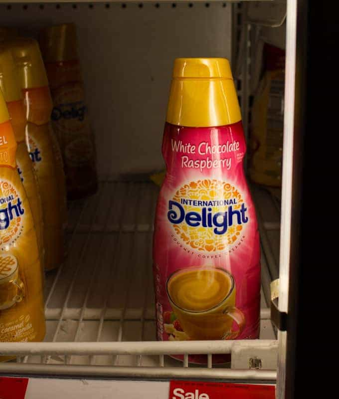 Bottles of coffee creamer on a rack inside a store refrigerator.