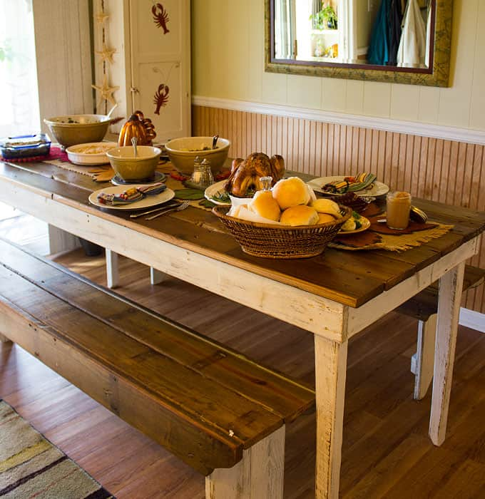 A wood kitchen table with benches.  A turkey and side dishes are on the table.