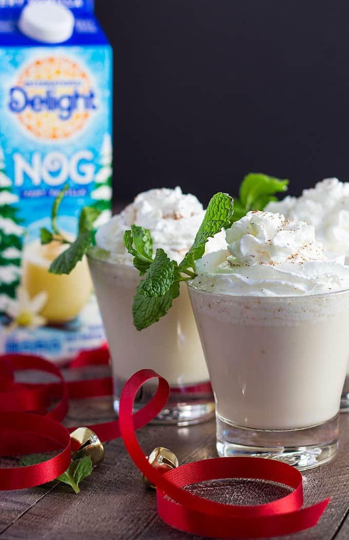 Three cocktails topped with whipped cream and mint sprigs.  A carton of nog is in the background.