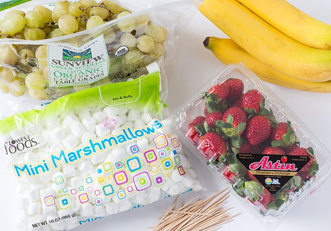 Overhead view of a bag of grapes, strawberries, marshmallows, bananas and toothpicks.