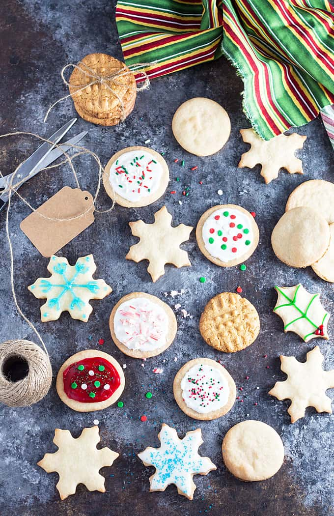 Overhead view of an assortment of decorated holiday cookies by a striped napkin.