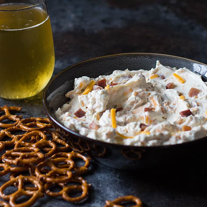 Front view of a blue bowl of dip by pretzels and a glass of beer.