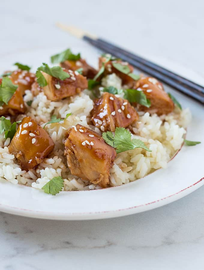 Closeup view of cubed chicken with an orange glaze over rice on a white plate with chopsticks.