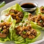Lettuce wraps with ground chicken on an oval white plate