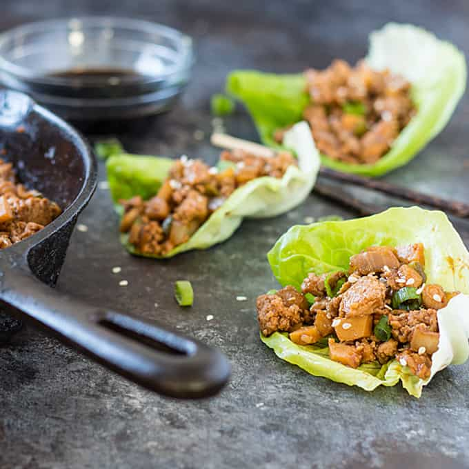 3 Asian Chicken Lettuce Wraps beside chopsticks, a cast iron skillet with chicken mixture and a bowl of soy sauce.