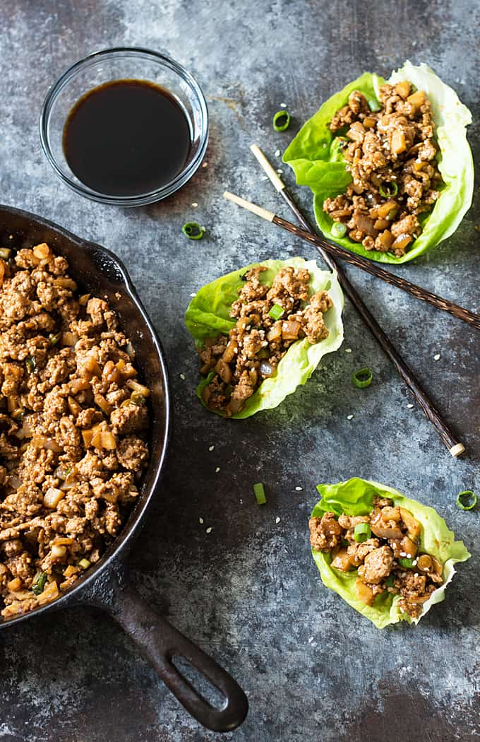 Overhead shot of 3 Asian Chicken Lettuce Wraps with chopsticks, soy sauce and a cast iron skillet with chicken mixture.