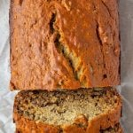 A partially sliced loaf of banana bread with overlay text.