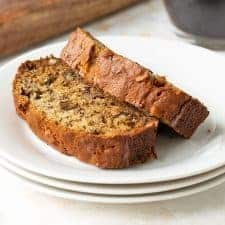2 slices of banana nut bread on a white plate. A cup of coffee is in the background.