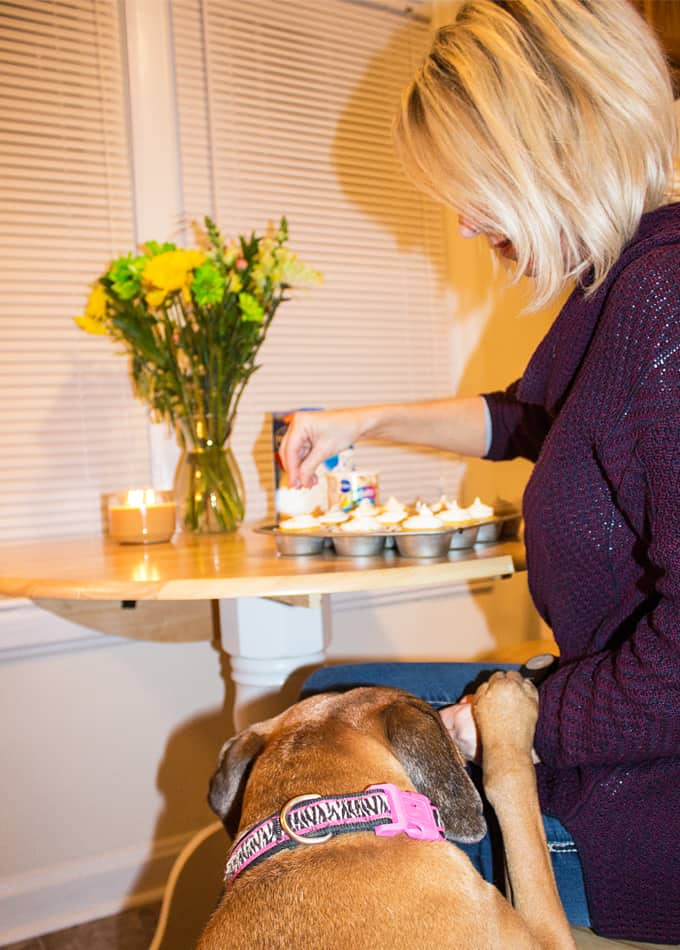 A woman with blonde hair decorating cupcakes at a kitchen table. Her dog is at her side.