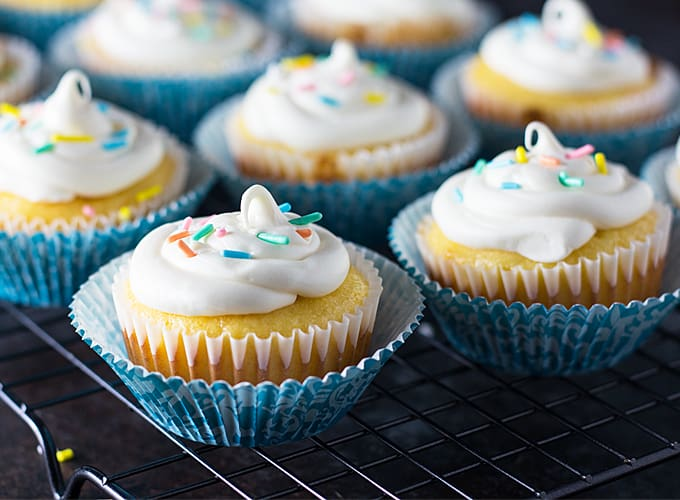 A closeup of frosted cupcakes in blue cupcake liners on a cooling rack.