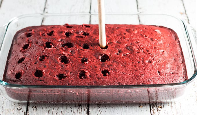 The handle of a wooden spoon poking holes in a red cake in a baking dish.