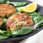 Salmon Patties in a black plate over fresh spinach with a fork