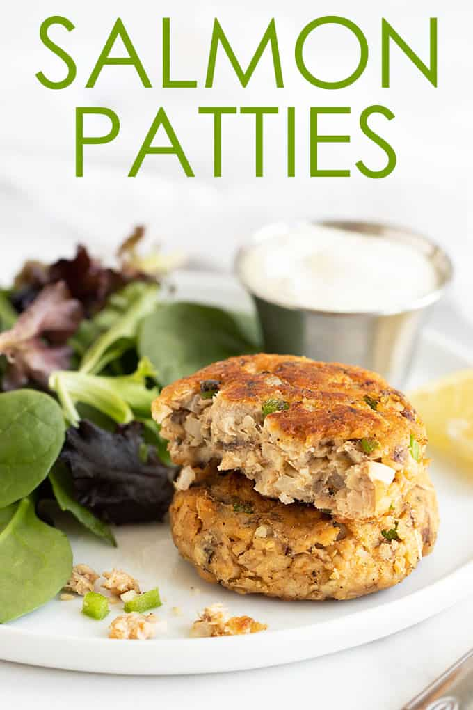 2 stacked salmon patties on a plate with a green salad, tartar sauce and a lemon wedge. Overlay text at top of image