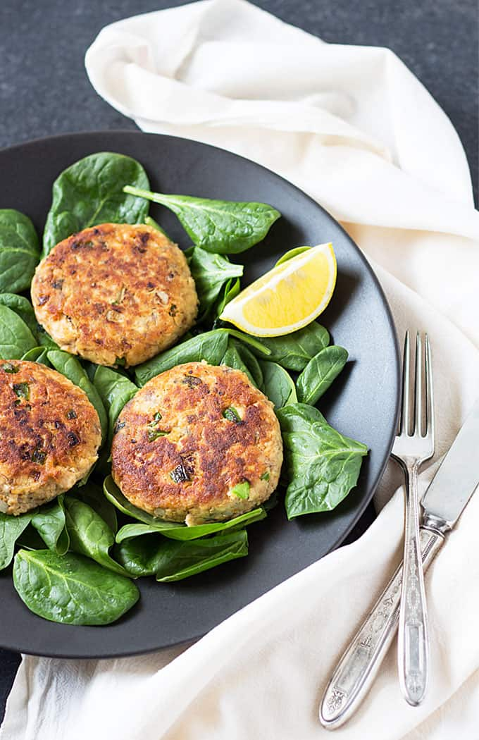 Overhead view of 3 salmon patties over fresh spinach on a black plate with a fork and knife
