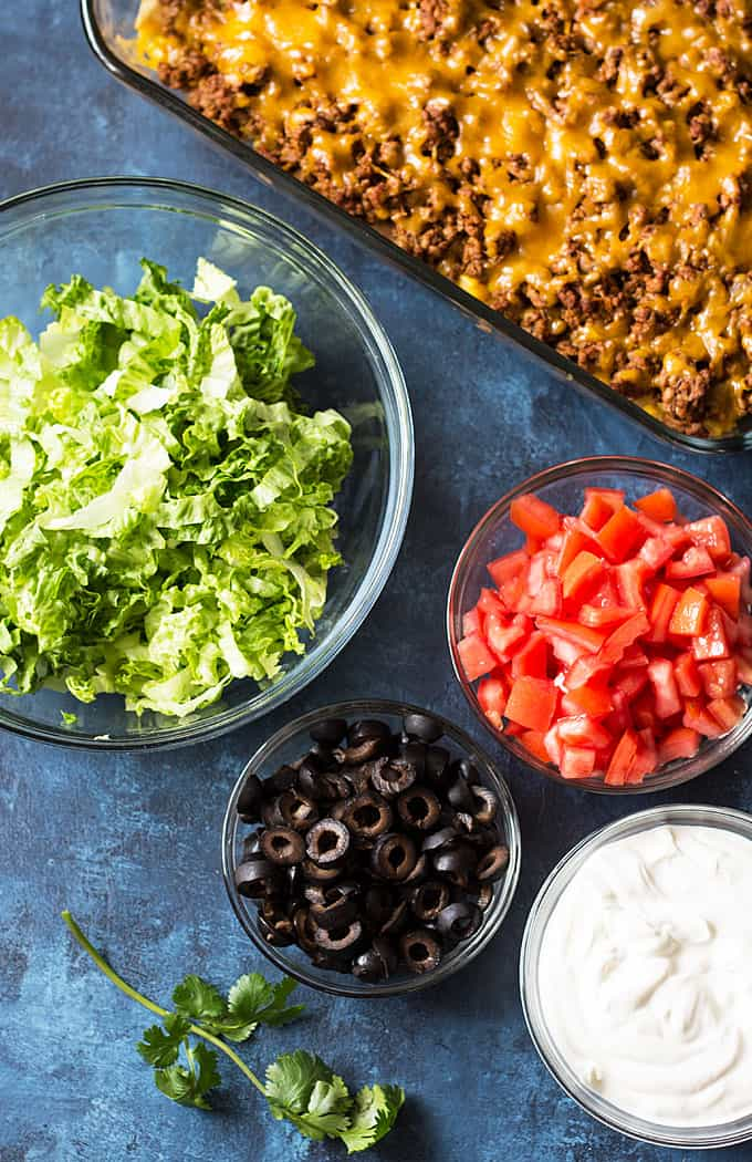 Overhead view of lettuce, tomatoes, sour cream, black olives and ground beef topped with cheese in a baking dish.