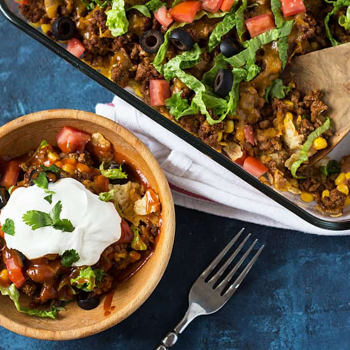 Overhead view of baked taco casserole topped with sour cream in a wood bowl.