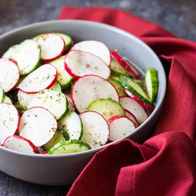 Front view of sliced cucumbers and radishes in a vinaigrette in a gray bowl.