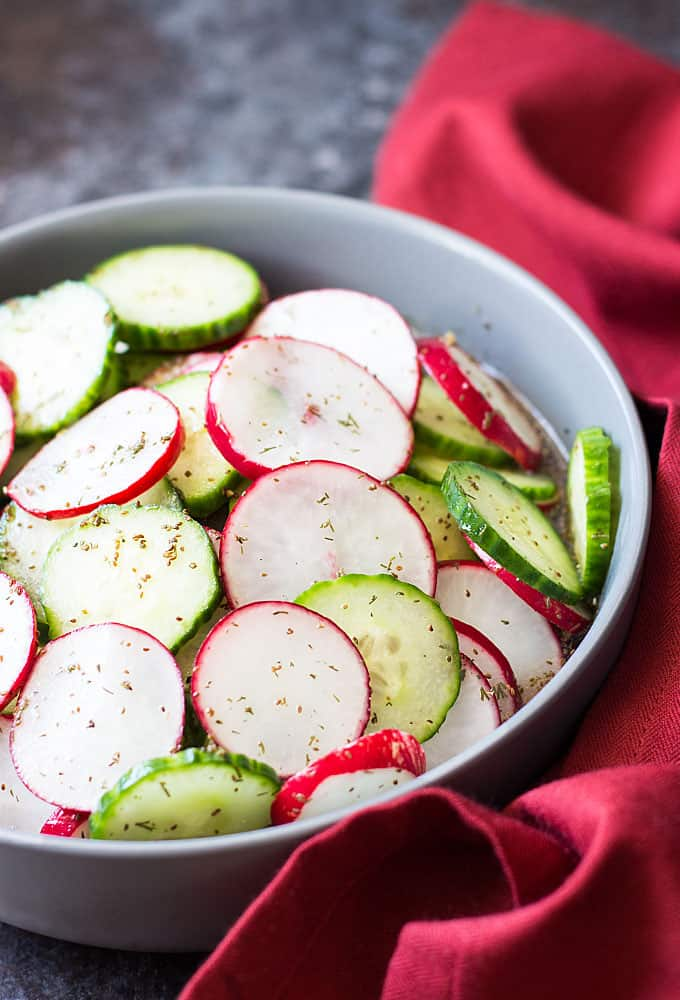 Front closeup view of sliced cucumbers and radishes in a dill vinaigrette in a gray bowl.
