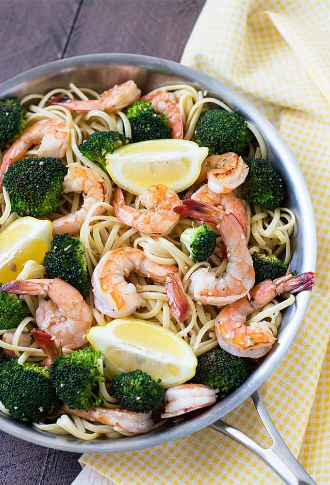 Overhead view of pasta with shrimp and broccoli in a skillet beside a patterned napkin.