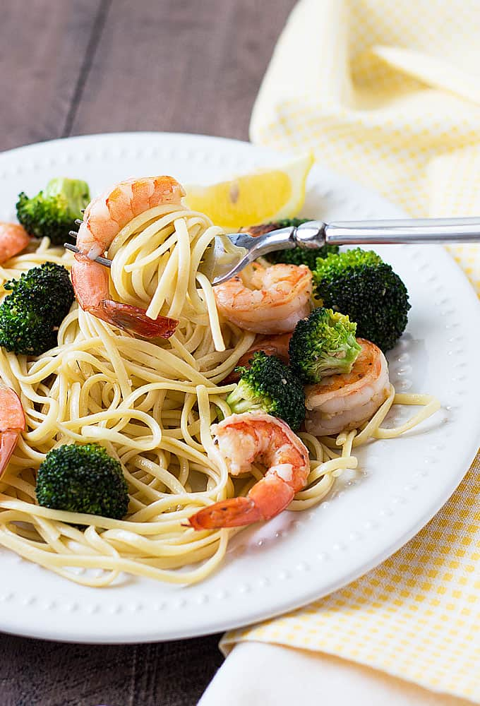 Pasta with shrimp and broccoli on a round white plate with a fork.