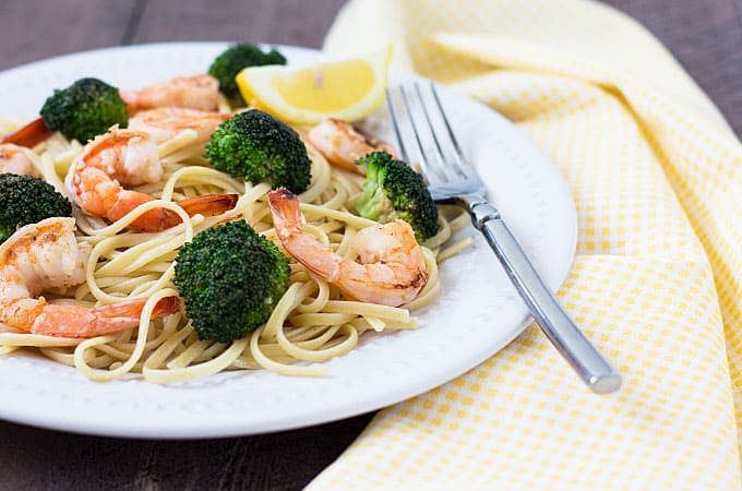 Front view of pasta topped with shrimp and broccoli on a white plate with a fork.