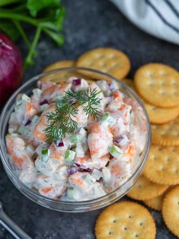 Shrimp Salad in a glass bowl beside round buttery crackers