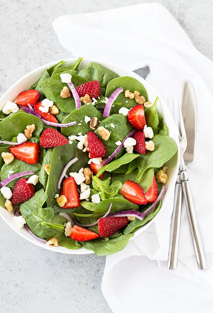 Overhead view of a spinach salad with strawberries, red onion, feta cheese and walnuts.